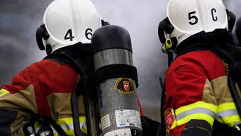 Nach Ausbruch eines Brands in einer Abfallverwertungsanlage in Sitten sind Feuerwehrleute mit Löscharbeiten beschäftigt. (Symbolbild)
