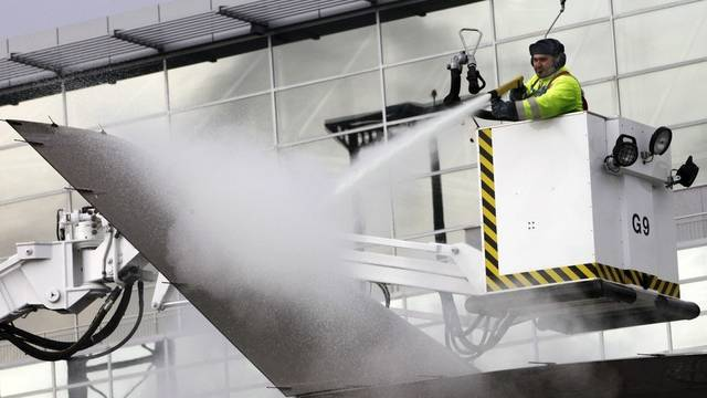 Ein Mitarbeiter enteist am Flughafen Frankfurt die Tragfläche eines Flugzeugs (Symbolbild)