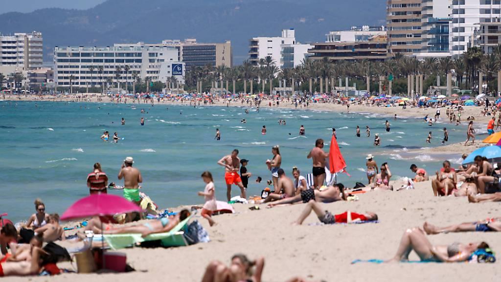 Menschen sonnen sich tagsüber am Strand von Arenal auf Mallorca. Nach einem Urteil des Obersten Gerichtshofs in Spanien sind die noch Corona-Beschränkungen bezüglich der Versammlungsfreiheit und auch die nächtliche Ausgangssperre nicht zulässig. Foto: Clara Margais/dpa