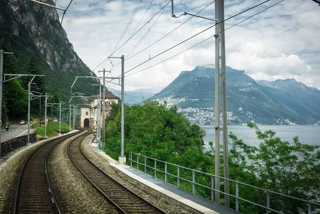 Bel Ticino – der Zug fährt den Luganersee entlang, rechts hinten majestätisch der Monte Brè.