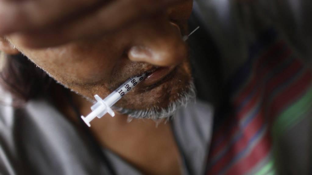 Ein Heroinkonsument in Puerto Rico hält die Spritze zwischen den Zähne - die Droge wird weltweit wieder häufiger konsumiert.