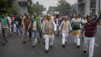 Eine Gruppe indischer Bauern protestiert auf dem Weg zum Wohnsitz des regierenden Mahesh Sharma der Bhartiya Janata Partei. Indische Bauern reichten beim Obersten Gerichtshof eine Petition ein, in der sie die Aufhebung von drei neuen Gesetzen zur Agrarreform fordern. Foto: Altaf Qadri/AP/dpa