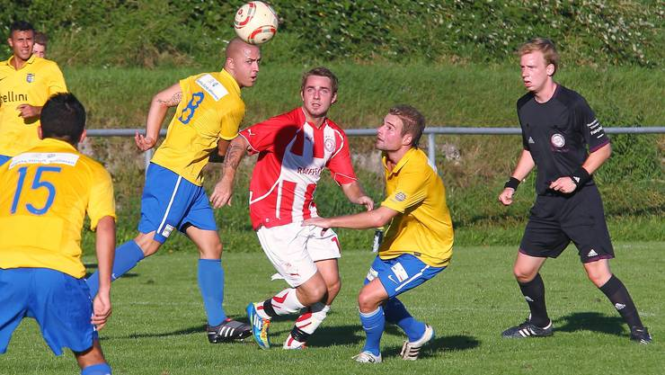Die Schlieremer Dario Marjanovic (in Gelb, rechts) und Sladjan Peric (Nummer 8) versuchen Remo Riedener aufzuhalten.