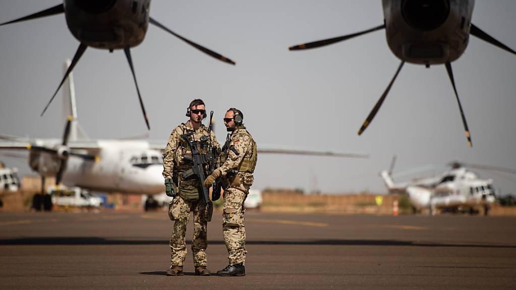 ARCHIV - Deutsche Soldaten stehen am Flughafen in Gao und sichern ein Transportflugzeug. Foto: Arne Immanuel Bänsch/dpa