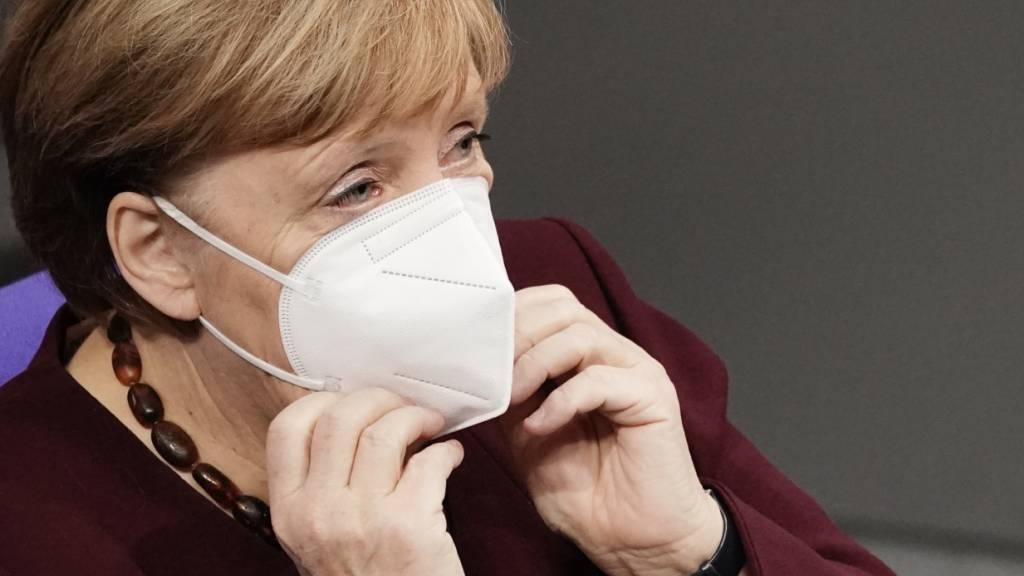 Bundeskanzlerin Angela Merkel setzt sich im Bundestag, nach der Regierungserklärung zur Bewältigung der Corona-Pandemie, ihre Maske auf.
