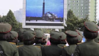 ARCHIV - Menschen stehen am im August 2017 auf dem Platz vor dem Hauptbahnhof in Pjöngjang, um die Übertragung eines Raketentests zu beobachten. Foto: Kim Kwang Hyon/AP/dpa