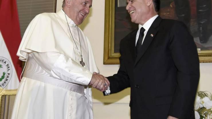 Paraguays Staatspräsident Horacio Cartes begrüsst Papst Franziskus: Das Oberhaupt der katholischen Kriche fand lobende Worte für das südamerikanische Land, mahnte aber zu weiteren Anstrengungen.
