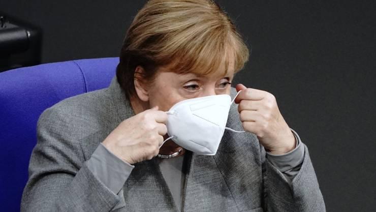Bundeskanzlerin Angela Merkel (CDU) nimmt mit Mund-Nasenbedeckung an der Debatte vor der Verabschiedung der Änderung des Infektionsschutzgesetzes, dem Gesetzes zum Schutz der Bevölkerung bei einer epidemischen Lage von nationaler Tragweite, teil. Foto: Kay Nietfeld/dpa