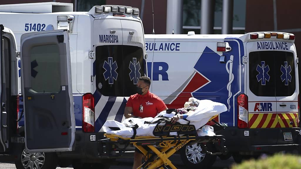 ARCHIV - Medizinisches Personal schiebt während der Corona-Pandemie vor Krankenwagen und Krankentransportern eine Patientin auf einer Trage vor dem Eingang der Notaufnahme des Ärztehauses «Banner Desert Medical Center» auf einen Krankentransporter zu. Foto: Ross D. Franklin/AP/dpa