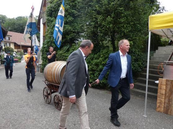 Unter Trommelwirbeln von Tambouren zog der kleine Festumzug durchs Gelände des Räbfeschts in Oberflachs. Regierungsrat Markus Dieth (links) und OK-Präsident Stefan Käser ziehen das Weinfass auf einem Wagen.
