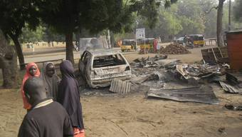 Hier jagten sich am Sonntag zwei Selbstmordattentäterinnen in die Luft: Kinder neben einem zerstörten Gebäude in Potiskum.