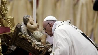 Christmesse im Petersdom: Papst Franziskus küsst bei eine Statue des Jesuskinds.