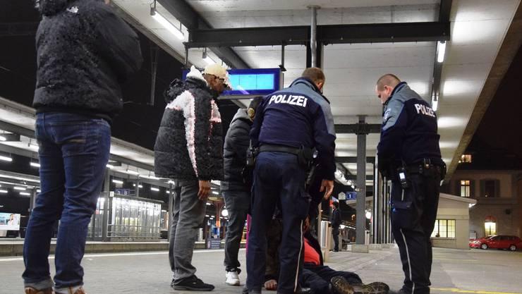 Am Bahnhof kann sich ein Betrunkener nicht mehr auf den Beinen halten.