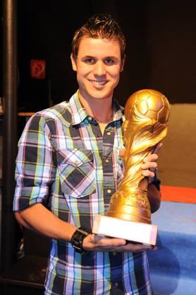 Riehen-Stürmer Dennis Uebersax nimmt zum dritten Mal den alten Pokal in Empfang.