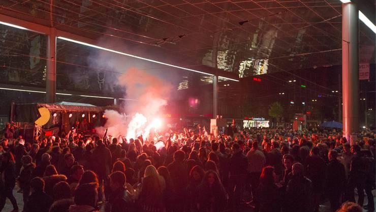 Tanzende Menge Pyrofackeln unter dem Baldachin beim Bahnhofplatz