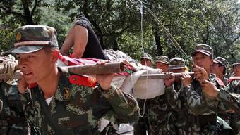 Chinesische Soldaten transportieren eine vom Erdbeben verletzte Person