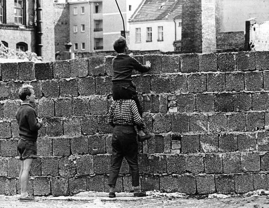 Neugierige Berliner Kinder wagen am 23. August 1961 über die frisch errichtete Mauer im Berliner Bezirk Wedding einen Blick nach Ostberlin