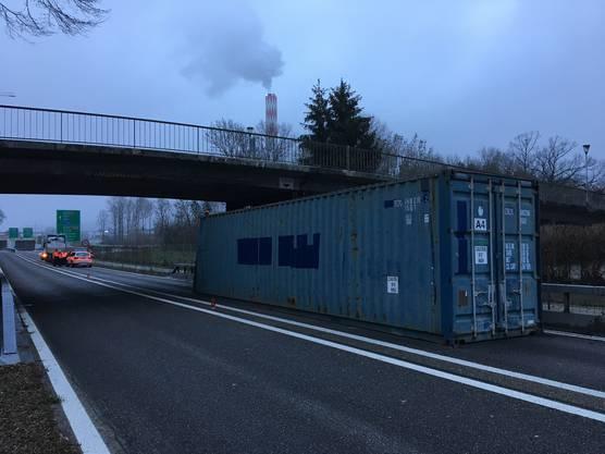Ein Schiffscontainer eines Sattelmotorfahrzeugs ist mit einer Brücke kollidiert und rutschte auf die Fahrbahn.