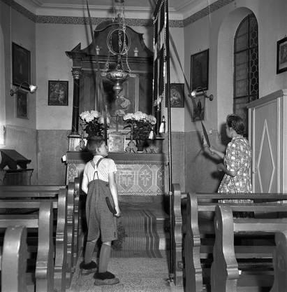 Eine Frau und ein Junge läuten die Kirchenglocken in einer kleinen Kirche im Aargau.