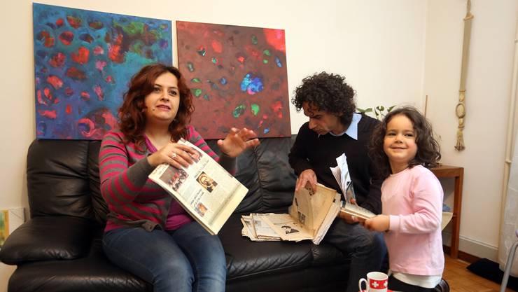 Lamen Ahmad ist stolz auf ihren Mann Salam Ahmad (r.). Rosselle (4) lacht gerne. An der Wand sind Ahmads Bilder zu sehen.