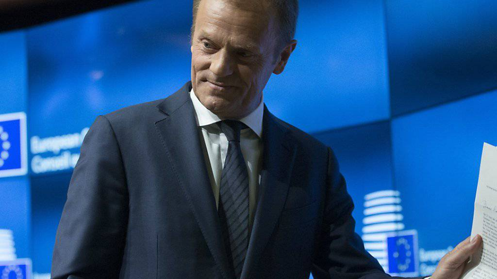 EU-Ratspräsident Donald Tusk hält das Austrittsgesuch der Briten aus der EU in die Kameras. Der britische EU-Botschafter Tim Barrow hatte es ihm am Mittwoch in Brüssel überreicht.