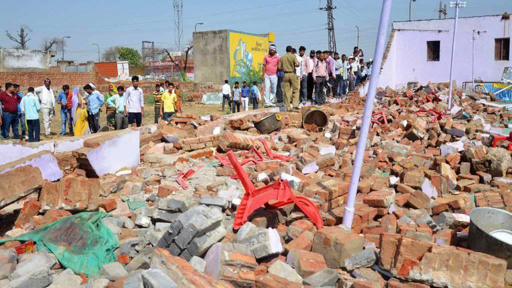 Plastikstühle ragen aus den Trümmern nach dem Einsturz der Mauer.