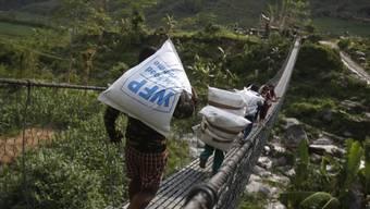 Nepalesen tragen Hilfsgüter des Welternährungsprogramms (WFP), nach dem verheerenden Beben in Nepal im vergangenen April