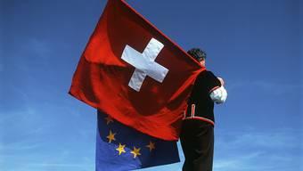 Ein Fahnenschwinger mit den Flaggen der Schweiz und der EU (Symbolbild)