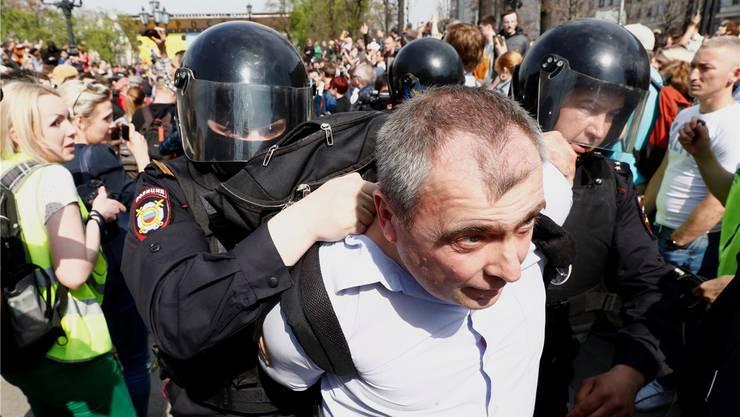 Polizisten führen in Moskau einen Demonstranten ab. Keystone