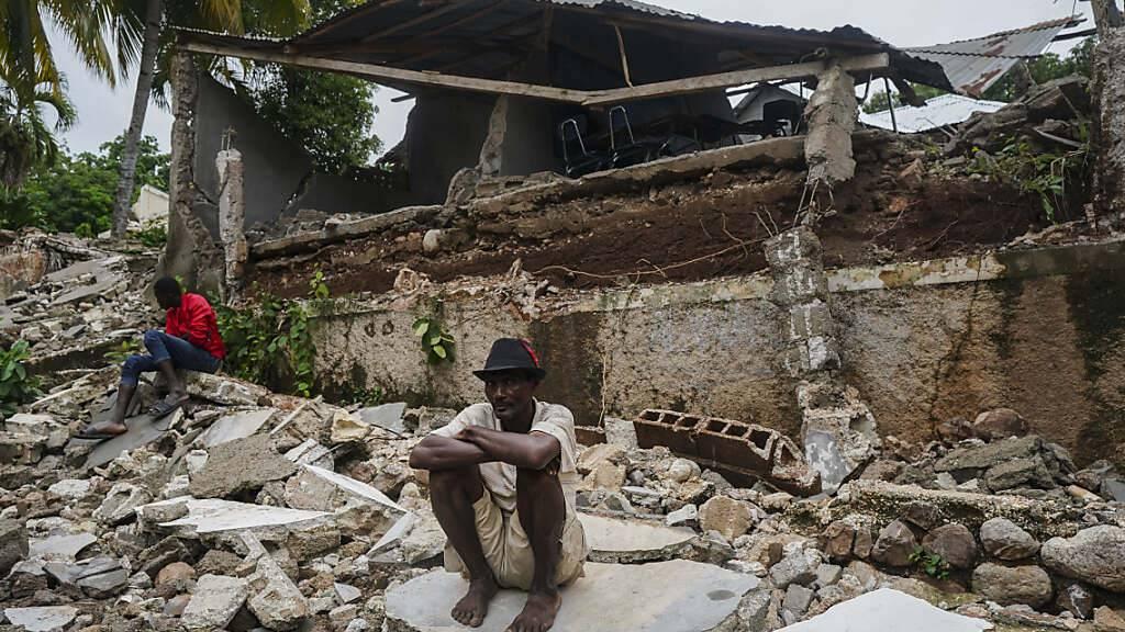 Ein Mann hockt auf den Trümmern des durch das Erdbeben zerstörten Krankenhauses in Fleurant. Die vorläufige Zahl der Erdbeben-Todesopfer in Haiti ist noch einmal deutlich gestiegen. Die haitianische Zivilschutzbehörde meldete am Dienstag via Twitter 1941 Tote und mehr als 9900 Verletzte. Foto: Fernando Llano/AP/dpa