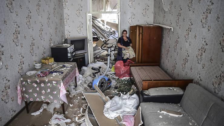 Eine Frau steht in ihrem beschädigten Haus, welches durch Beschuss durch armenische Soldaten beschädigt wurde. Foto: Ismail Coskun/AP/IHA/dpa