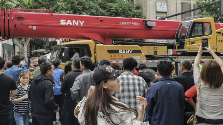 Schaulustige beobachten die Ankunft eines LKW-Hebekrans nach dem Einsturz eines Gebäudes in der Nähe.