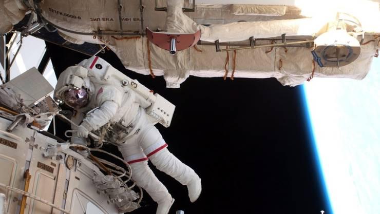 Archivbild eines ISS-Ausseneinsatzes. Dieses Mal mussten zwei Kosmonauten unter anderem die Glasscheiben an den Lichtluken reinigen. (Archivbild)