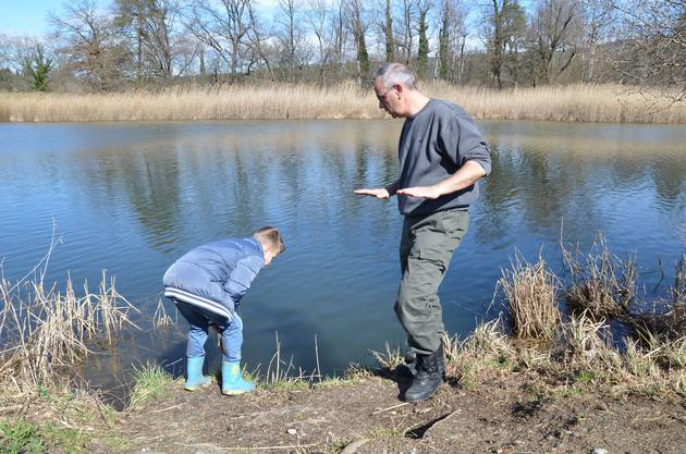 Vereinspräsident Patrick Grau erklärt Jungfischer Colin Klauser, wie das Reusswasser aus dem Dammspitz in die Kalberweid gelangt, wo sich Hechte und Karpfen gerne aufhalten.