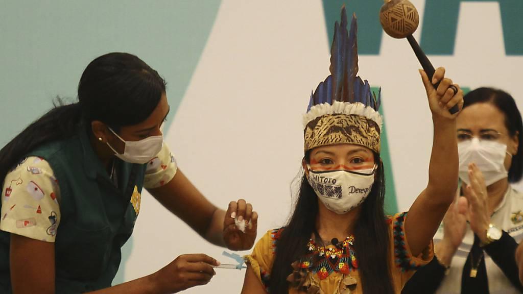Die in traditioneller Kleidung gekleidete Gesundheitsmitarbeiterin Vanda Ortega von der indigenen Gruppe der Witoto wird geimpft. Foto: Edmar Barros/AP/dpa