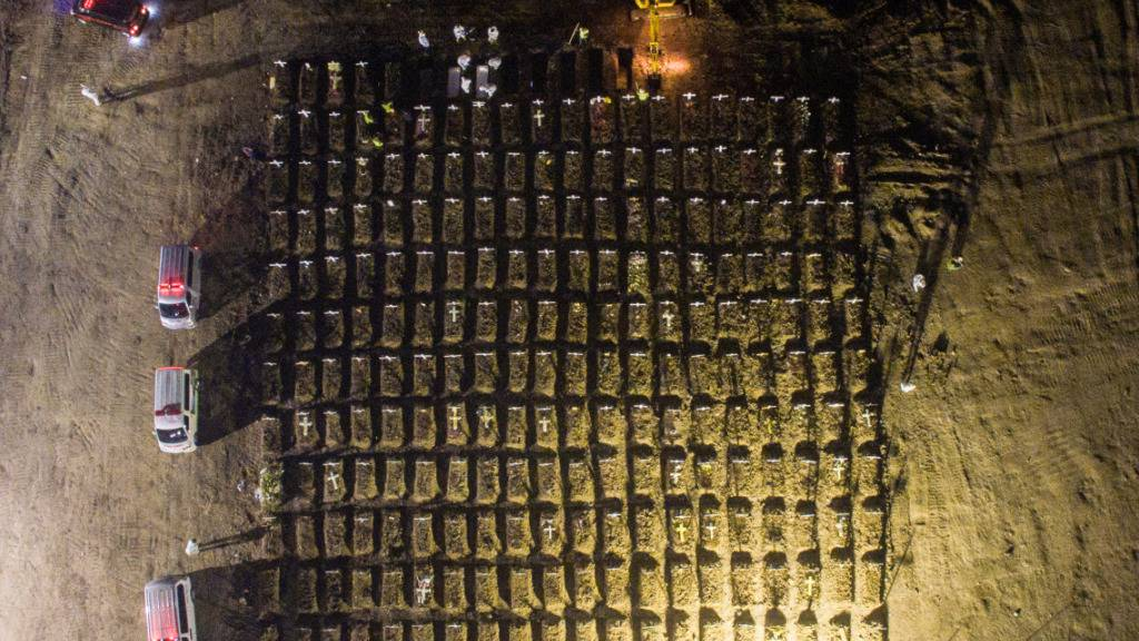 dpatopbilder - In Jakarta stehen Mitarbeiter (oben) in weißer Schutzkleidung um Gräber herum, während neben ihnen ein Bagger weitere Gräber aushebt. In Indonesien sind mehr als 69 000 Menschen in Verbindung mit Covid-19 gestorben. Foto: Wisnu Prasetyo/SOPA Images via ZUMA Wire/dpa