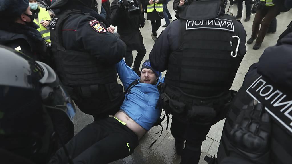 dpatopbilder - Die Polizei trägt einen Mann weg während eines Protestes in Moskau gegen die Inhaftierung des Oppositionsführers Nawalny. Foto: Uncredited/AP/dpa