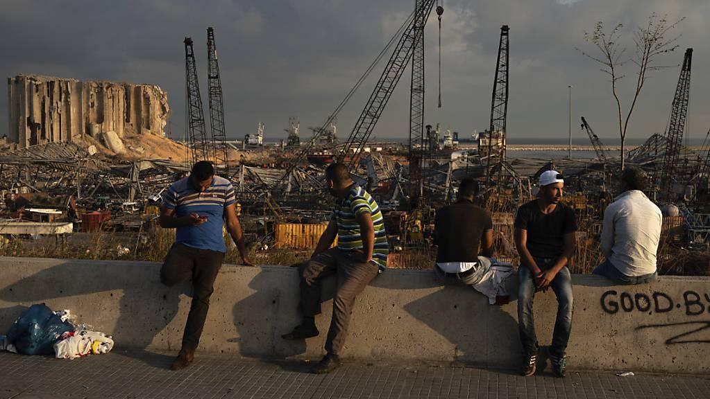 Menschen sitzen in der Nähe des Ortes der verheerenden Explosion im Hafen Beiruts.