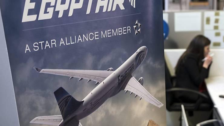 Eine Angestellte von Egyptair telefoniert an ihrem Schalter am Pariser Flughafen Charles de Gaulle. Laut ägyptischen Angaben sind erste Trümmerteile des verschwundenen Flugzeugs gefunden worden.