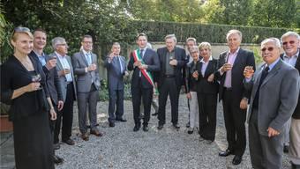 Argo Lucco (M.) hebt bei der Jubiläumsfeier das Glas, neben ihm der italienische Konsul in Basel Michele Camerota (r.) sowie Birstaler Gemeindevertreter (l.).