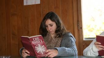 Eine Schülerin liest in der Bibel.
