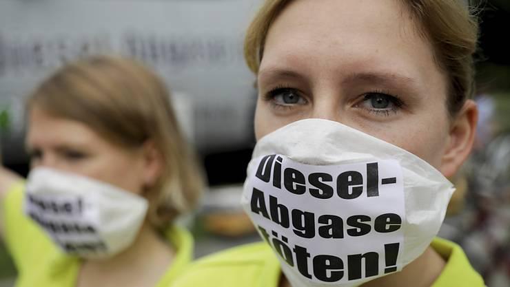 Demonstranten am Diesel-Gipfel in Deutschland fordern deutliche Reduktionen der Abgase, während sich die Autohersteller auf eine freiwillige Nachrüstung einigten.