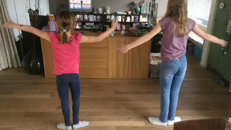 Zwei balladyum-TänzerInnen, die zu Hause mit Anleitung vom Video aus ihrer Tanzschule tanzen.