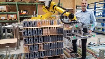 Nick Koch, CEO der Robotec Solutions, steht vor einem Roboter, der die abgefüllten Flaschen auf eine Palette stapelt.