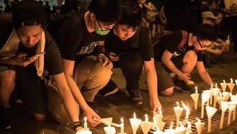 Protestierende in Hongkong ehren das erste Todesopfer mit Kerzen.