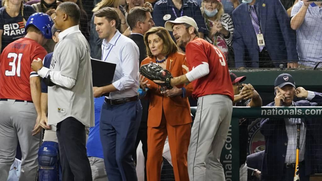 Präsident Joe Biden (r) telefoniert, während die Sprecherin des Repräsentantenhauses, Nancy Pelosi (M, Kalifornien) das Baseballspiel des Kongresses verfolgt. Inmitten angestrengter Verhandlungen im US-Kongress haben sich Parlamentarier und Präsident Joe Biden eine Pause gegönnt - beim Baseball. Foto: Susan Walsh/AP/dpa