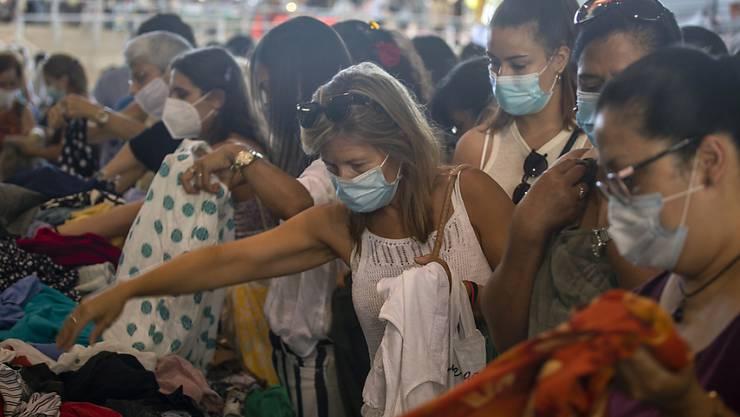 Kundinnen, die Mundschutz tragen, kaufen Kleidung an einem Stand auf einem Markt in Barcelona. Die spanische Region Katalonien führt eine ungewöhnlich strenge Maskenpflicht ein. Foto: Emilio Morenatti/AP/dpa