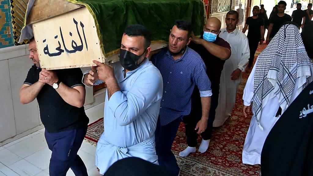 Trauernde tragen den Sarg eines Corona-Patienten, der bei der Explosion im Al-Khatib-Krankenhaus ums Leben kamen. Foto: Anmar Khalil/AP/dpa