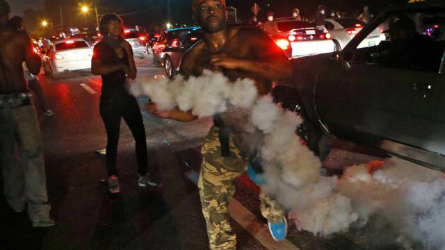 Ein Demonstrant wirft eine Tränengaspatrone zur Polizei zurück