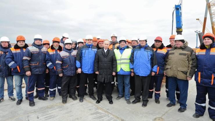 Wladimir Putin (Mitte) posiert am Freitag mit Arbeitern auf der Baustelle der ersten dauerhaften Brücke über die Meerenge von Kertsch.